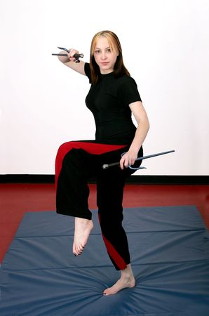 female mma student with sai weapons and ready to kick or fight