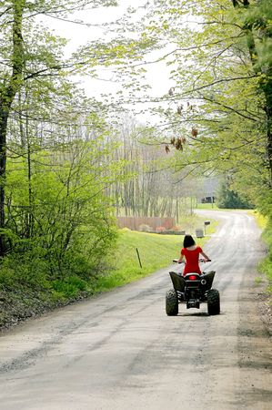 wheeler: young adult female riding a 4 wheeler on a dirt road Stock Photo