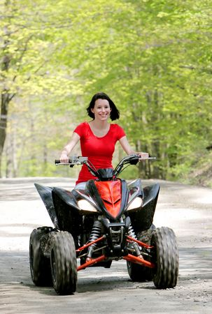 wheeler: oncoming close up young adult female riding a 4 wheeler on a dirt road