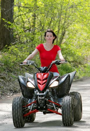 young adult female riding a 4 wheeler on a dirt road photo