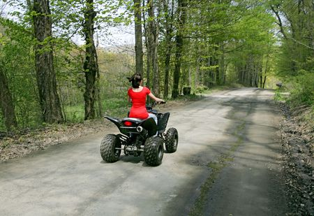 young adult female riding a 4 wheeler on a dirt road driving away photo