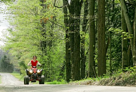 young adult female riding a 4 wheeler on a dirt road from low angle photo