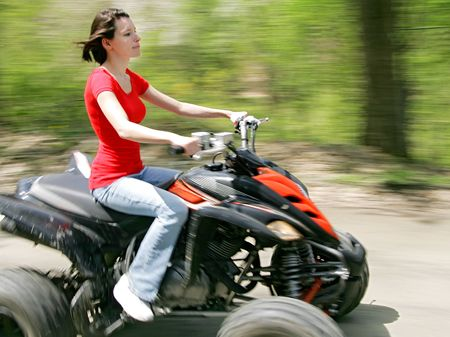 quad: young adult female riding a 4 wheeler on a dirt road with good panning motion blur