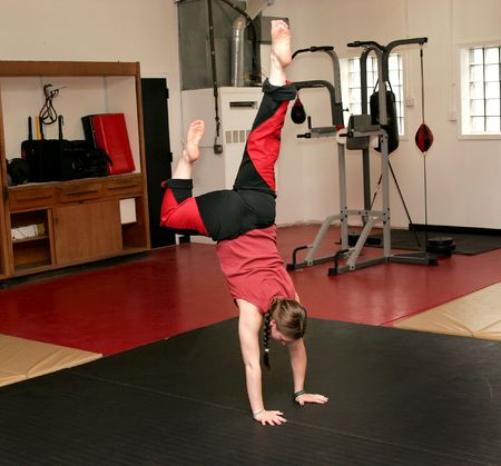 martial arts woman: young adult female performing a handstand in a dojo