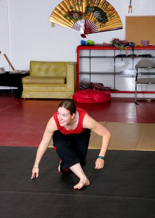 a young adult female performing capoeira dance martial arts moves