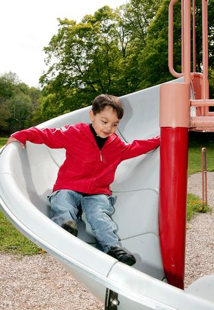 young male child playing on the slide at a playground Stock Photo - 3040784