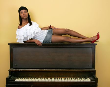 a sexy beautiful African American woman sitting on top of a piano photo