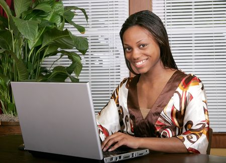 African American female adult working at a laptop computer and smiling