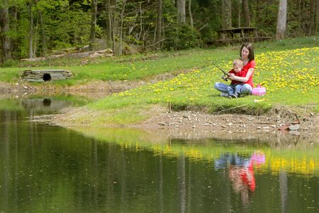 a woman and her young boy child go fishing at the pond 免版税图像