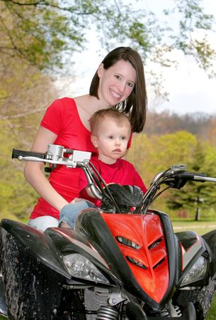 four wheel: adult female and young male child riding on a four wheel all terrain vehicle in the woods