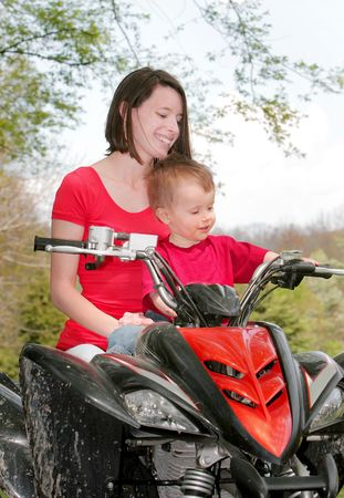 adult female and young male child riding on a four wheel all terrain vehicle in the woods photo