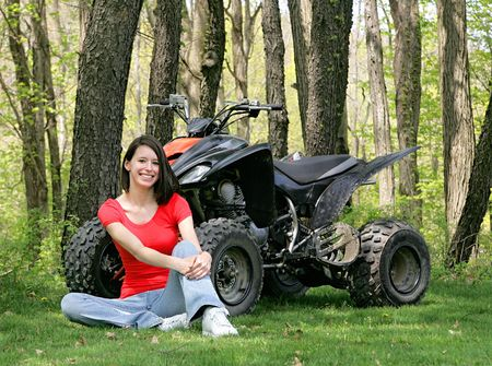 dark haired woman: young adult female sitting beside a black and orange ATV four wheel vehicle Stock Photo