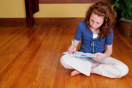 a young female child sitting on the hardwood floor and writing in a journal or diary Banque d'images