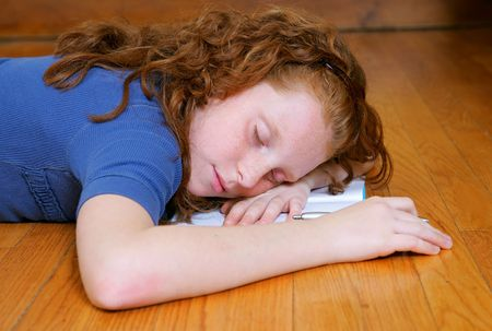 hardwood: a young female child laying down sleeping on her diary or journal
