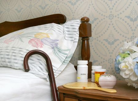 frail: medicine bottles and a cane against a bed for an elderly person