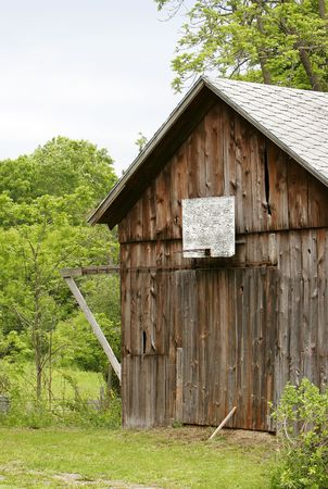 brown old weathered barn with a broken basketball hoop on the side photo