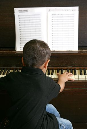 a male youth practicing songs on the piano keys Stock Photo - 3110388