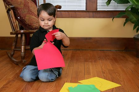 a young male child cutting paper strips on the floor photo