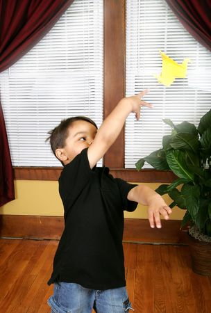 a young dark haired boy throwing a yellow Japanese Crane made by origami photo