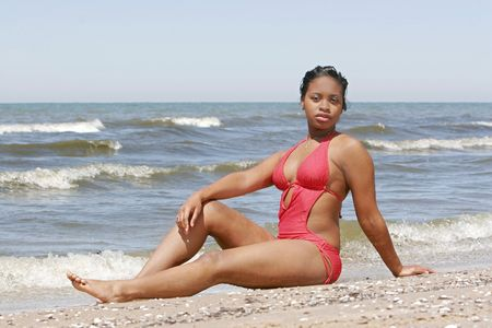 beautiful African American woman in a swimsuit sitting on the beach Stock Photo