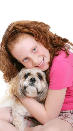 a young red haired girl holding her dog close over white photo
