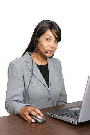 an adult female customer service representative with her headset on ready to work at her laptop photo