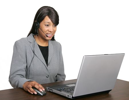an adult female customer service representative with her headset on ready to work at her laptop