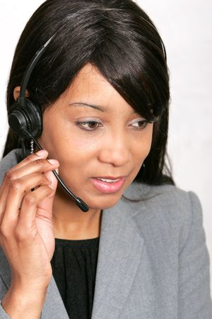 an adult female customer service representative with her headset on ready to work
