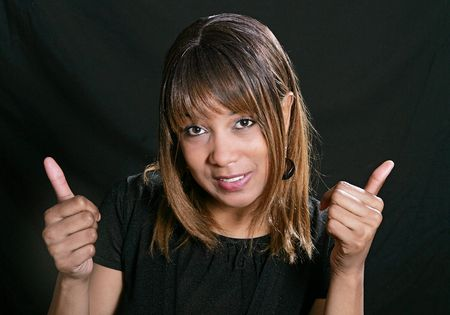 African American woman over a black background giving two thumbs up and smiling photo