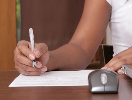 person writing: African American woman writing on a piece of paper near a workstation