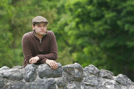 portrait of a young male with brown hair in the park on a stone bridge Stock Photo - 3137827