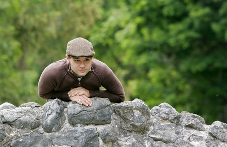 portrait of a young male with brown hair in the park on a stone bridge Stock Photo - 3137786