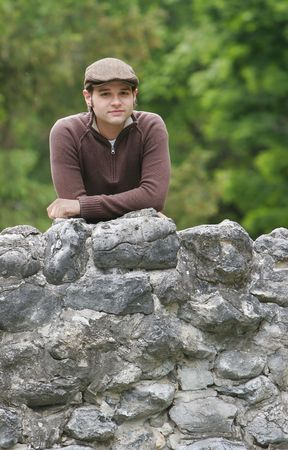 portrait of a young male with brown hair in the park on a stone bridge Stock Photo - 3137864