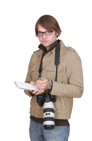 a young male photojournalist with a large camera and notebook over white Stock Photo
