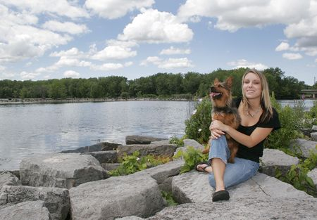 a blonde haired girl holding her dog near the water in a park photo