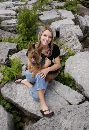 a blonde haired girl holding her dog in a park photo