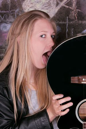 young moody adult female rocker licking her guitar photo