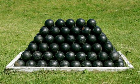 firepower: a canonball stack of 18 pound black ammunition in the grass Stock Photo