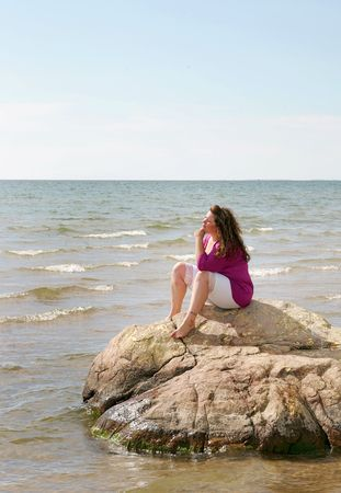 plus sized: a young plus sized model sitting on a large rock in the ocean or lake