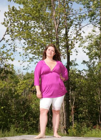a  young plus sized female model standing and thinking