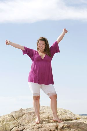 a  young plus sized female model standing and reaching to the sky
