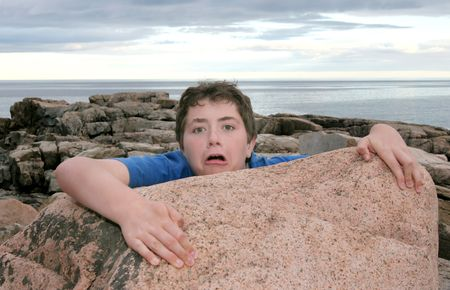 falling down: a young boy child falling off a rock on the coast
