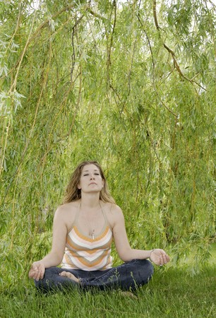 one young adult woman doing yoga and relaxing under trees outdoors in a park during summer Banque d'images