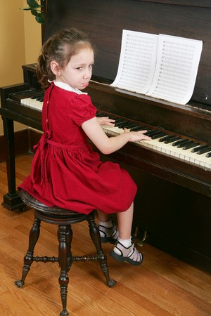 one young child sitting at the piano looking very unhappy