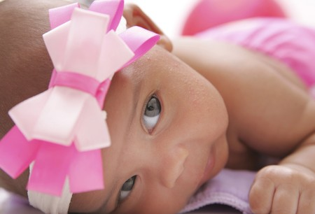 one portrait of a young baby posing on a colorful cloth diaper over white closeup portrait