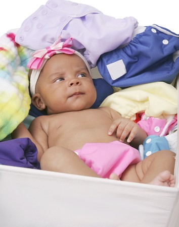 one young African American baby laying in a bucket of clean cloth diapers over white Stock Photo