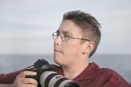 水に対する屋外の写真を撮る準備ができている彼のカメラを持つ男の肖像 写真素材