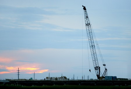 a crane silhouetted against a fading colorful sunset at dusk photo