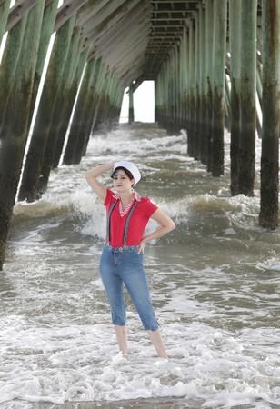 Une jolie femme en rouge, blanc et bleu marine porter posant dans le cadre de la jetée près de l'eau Banque d'images - 3952968