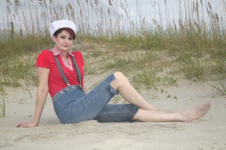 Une jolie femme en rouge blanc et bleu marin porter assis sur la plage posant Banque d'images - 3952988